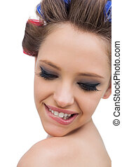 Model wearing hair curlers smiling in close up
