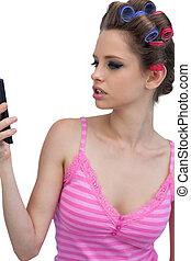 Model wearing hair rollers posing looking at the phone