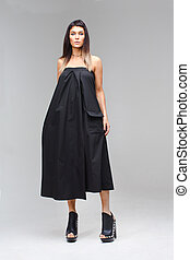 Model which holds the dress in hand black sundress
