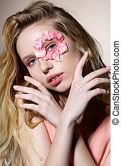 Model with flower petals near eye holding hands near face