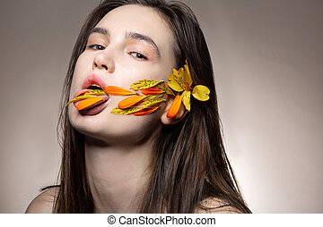Model with natural makeup posing with petals in mouth