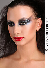 Model with smokey eyes and wild hair. Close up. Gray ...