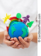 Modelling clay earth with rainbow and trees in child hands