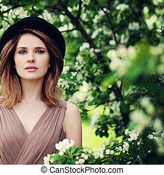 modelo, mujer, en, flores del resorte, jardín, outdoorswith, flores, plano de fondo