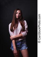 modelo, prueba, de, hermoso, morena, mujer, con, pelo largo, usa, suéter rosa, cortocircuitos azules, posar, en, un, fondo negro
