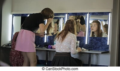 Models are busy with preparation for photo session in dressing room.