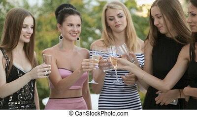 Models drinking champagne on the veranda
