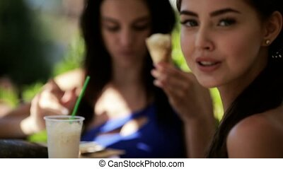 Models in bikini eating ice cream and drinking milkshakes at the outdoor cafe
