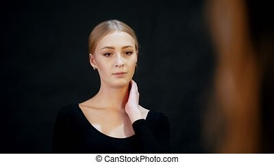 Models in the studio. A young blonde woman model posing for a photographer
