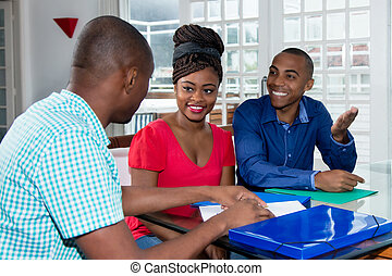 Modern african american couple with contract of real estate agent