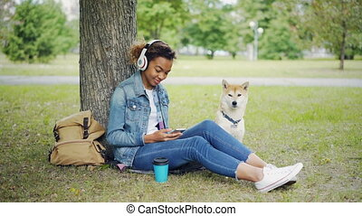 Modern African American girl is listening to music with...