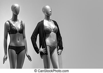 Modern and luxury shop of underwear. Full-length female mannequins in nderwear. Lingerie on plastic dolls in store window display. Sale and advertising theme. Copyspace for text