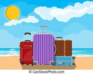 Modern and vintage travel bag on beach.