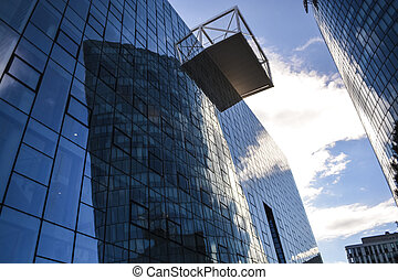 Modern architecture of office buildings. A skyscraper from glass and metal. Reflections in windows of blue sky. Business center