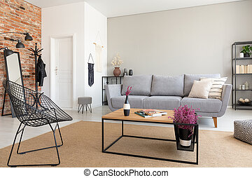 Modern armchair next to wooden table in living room interior with grey sofa and flowers. Real photo