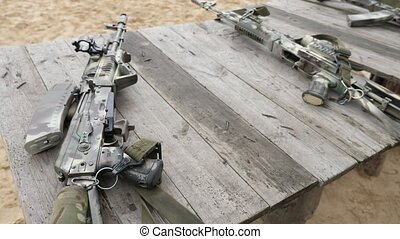 Modern assault rifle with optic sights lying on a wooden...