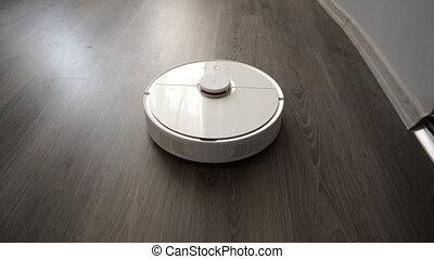 Modern autonomous robot vacuum cleaner slides on the...