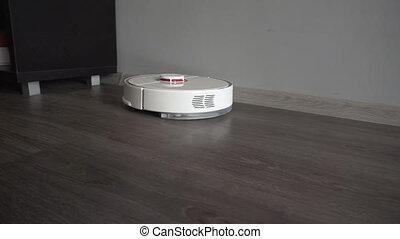 Modern autonomous robotic vacuum cleaner in the apartment. -...