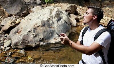 Modern backpacker - Backpacker standing in mountain river...