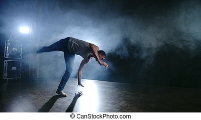 Modern ballet, a man from a sitting position on the stage jumps backflip with rotation on a dark stage in the smoke in the spotlight