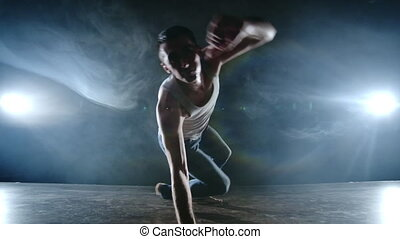 Modern ballet, a man from a sitting position on the stage jumps somersault with rotation to the camera on a dark stage in the smoke in the spotlight. Modern choreography on the stage of the theater.