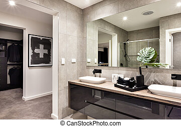 Modern bathroom closeup to a mirror and countertop sink and towels next to liquid soap, dressing room can be seen through the door