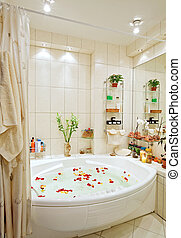 Modern bathroom in warm tones with jacuzzi and rose petals wide angle view