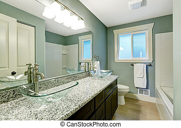 Modern bathroom interior with window. View of wooden vanity cabinet with granite counter top and glass vessel sinks