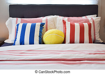 Modern bedroom interior with blue,yellow and red striped pillows on bed