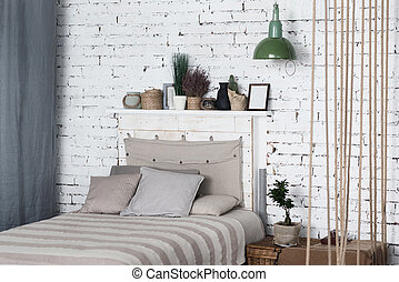 Modern bedroom with big grey bed in middle