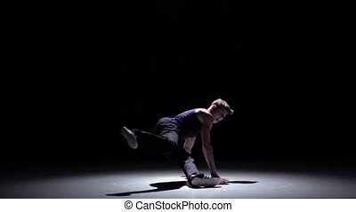 Modern blonde breakdance man jumping starts dancing on black, shadow, slow motion