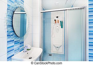 Modern blue bathroom interior with round mirror and shower ...