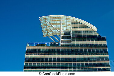 Modern Blue Glass Office Tower with Curved White Roof Under Sky