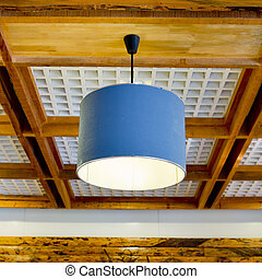 Modern blue hanging lamp on wooden ceiling