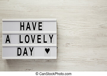 Modern board with text 'Have a lovely day' on a white wooden background, top view. From above, flat lay, overhead. Copy space.