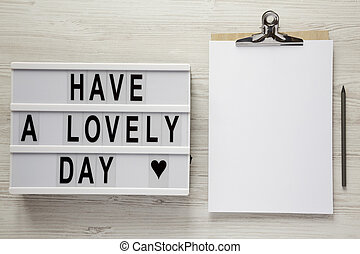 Modern board with text 'Have a lovely day', pencil and noticepad over white wooden background, top view. From above, flat lay, overhead.