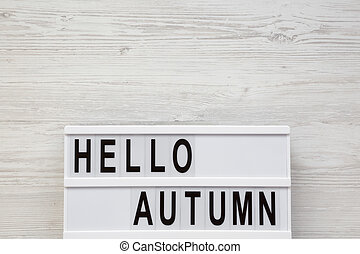 Modern board with text 'Hello Autumn' on a white wooden background, overhead view. Top view, flat lay, from above. Copy space.