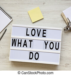 Modern board with text 'Love what you do', notepad, pencil and noticepad over white wooden background, top view. Business concept. From above, flat-lay, overhead.