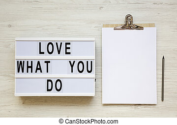 Modern board with text 'Love what you do', pencil and noticepad over white wooden background, top view. Business concept. From above, flat-lay, overhead.