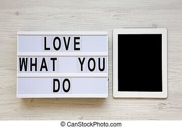 Modern board with text 'Love what you do', tablet over white wooden background, top view. Business concept. From above, flat-lay, overhead.