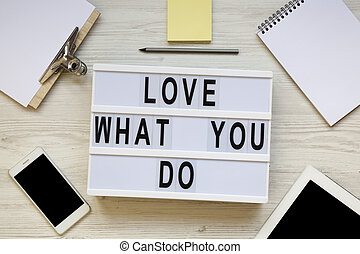 Modern board with text 'Love what you do', tablet, smartphone, notepad and pencil over white wooden background, top view. Business concept. From above, flat-lay, overhead.