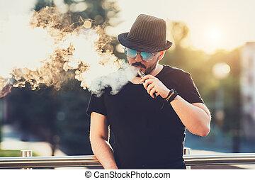 modern, boldog, fiatalember, alatt, kalap, noha, egy, szakáll, móka, vaporizers, alatt, a, háttér, a, este, napnyugta, felett, a, city., hanglejtés, image.