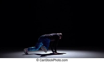 Modern breakdance man jumping continue dancing on black, shadow, slow motion