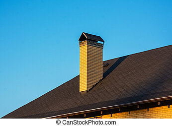 Modern brick chimney with beautiful forge. Clear blue sky background