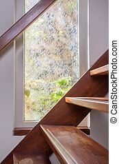 modern brown staircase with wooden floor and glass barrier