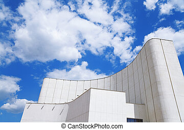 Modern building against the blue sky with clouds