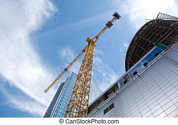Modern building under construction against blue sky