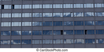 modern building windows reflecting blue sky close up