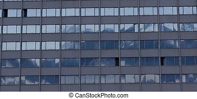 modern building windows reflecting blue sky