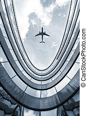 Modern building with flying airplane
